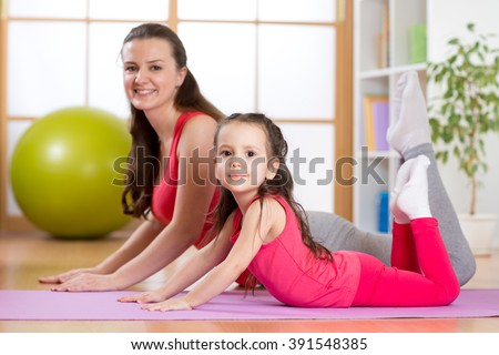 Mom and kid do gymnastics. Family sports - stock photo