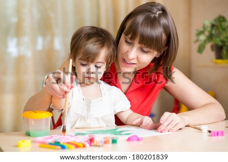 mom and kid girl paint together at home