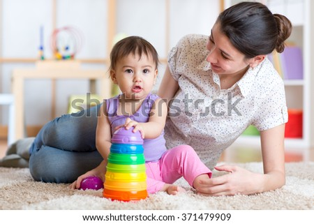 mom and kid playing block toys at home - stock photo