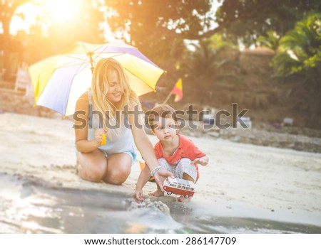 mom and kid playing on the beach. mom playing with toys car with her little son - stock photo