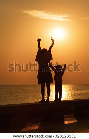 Mom and little daughter with their hands up to meet the sunrise over the sea. Silhouettes of women and girl. Toned image.