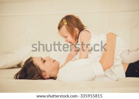 mom and little girl playing together in a cozy room - stock photo