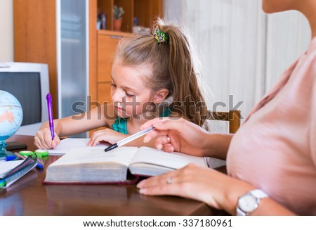 mom and little girl studying with notes at home