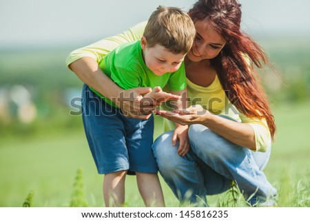 Mom and son consider a ladybug on a palm - stock photo