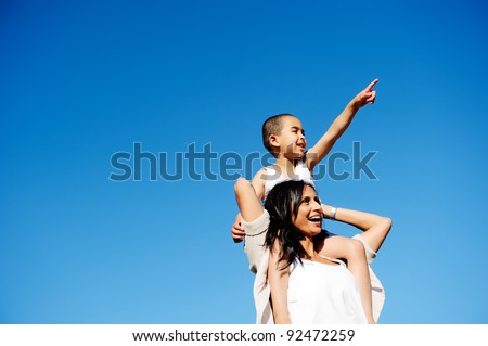 Mom and son happy and free outdoors in the blue sky. carefree cheerful concept - stock photo