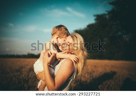 Mom and son having fun by the lake, field  outdoors enjoying nature. Silhouettes on sunny sky.  Warm filter and film effect - stock photo