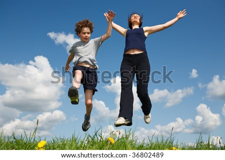 Mom and son jumping outdoor - stock photo