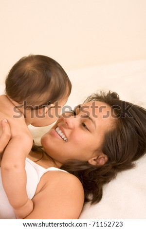 Mom and son on bed and mother embracing the infant baby playing with him - stock photo