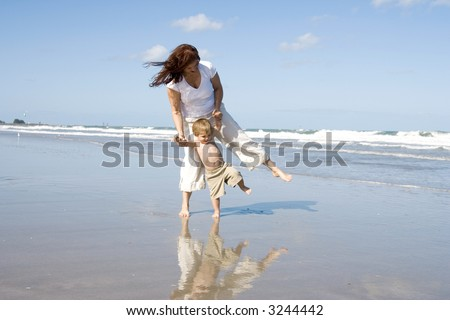 Mom and son playing on a beach, ocean and blue sky in the background - stock photo