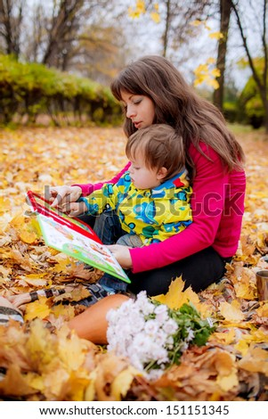 Mom and son  reading a book in the autumn garden - stock photo