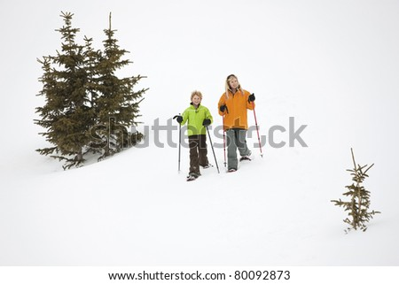 Mom and son running in snowshoes. - stock photo