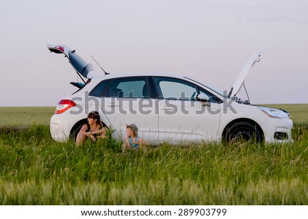 Mom and Son Sitting Beside their White Defective Car While Waiting for a Mechanic - stock photo