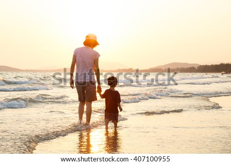 Mom and son walking on beach against bright sunlight, family love concept - stock photo