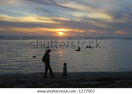 Mom and Son walking on the beach at sunset