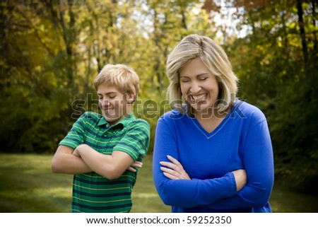Mom and son with arms crossed and laughing