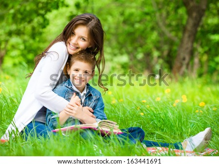 Mom and son with book sitting on green grass in green park. Concept of happy family relations and carefree leisure time - stock photo