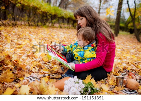 Mom and son 3 years reading a book in the autumn garden - stock photo