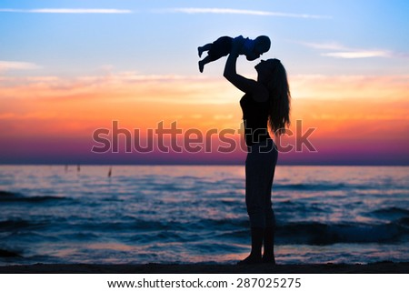 Mom and sun playing during beautiful sunset - stock photo