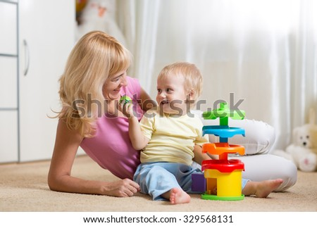 mom and toddler child boy playing with colorful logical toy at home