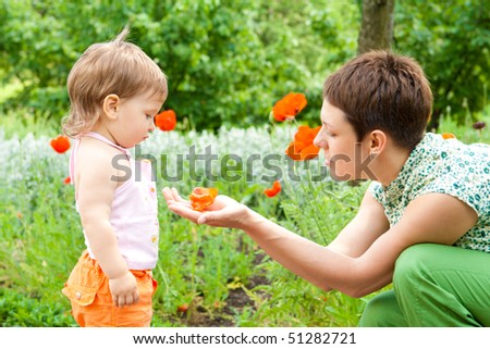 Mom and toddler girl in the garden - stock photo