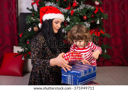 Mom and toddler son opening Christmas presents
