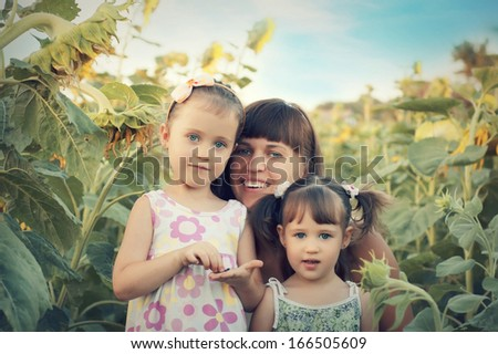 Mom and two lovely daughters in the field of sunflowers - stock photo