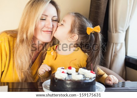 Mom and young daughter celebrating a birthday with cake - stock photo
