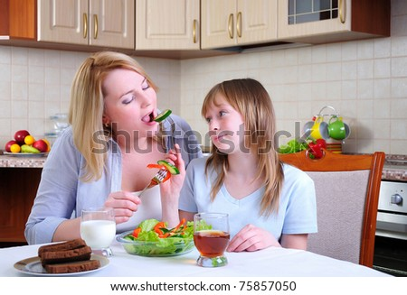 Mom and young daughter eating breakfast together in the kitchen - stock photo