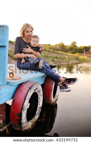 Mom and young son in a striped dress sitting on a wooden bridge on a background of the river