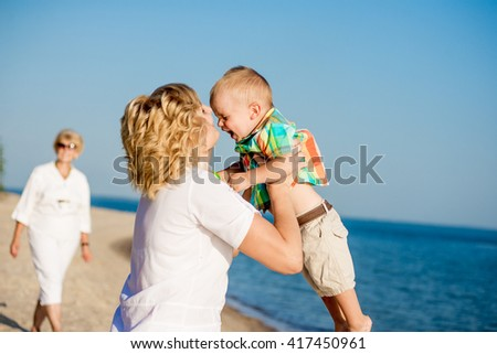 Mom and young son walking on the beach in summer