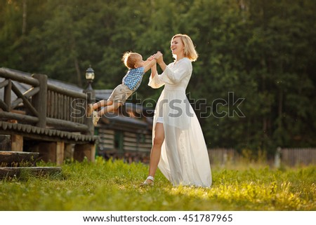 Mom blonde in white dress laughs and spins son at sunset in summer - stock photo