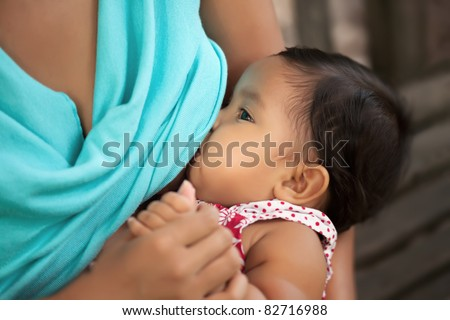 mom breast feeding her baby girl and holding her hand - stock photo