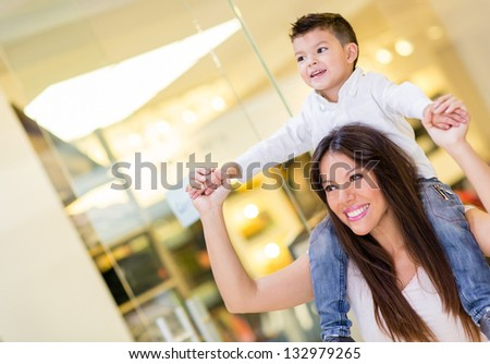 Mom carrying her son in her shoulders at the mall - stock photo
