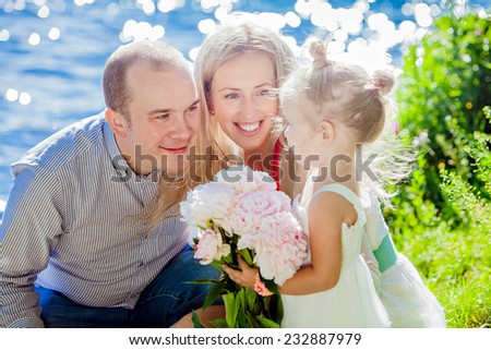 Mom, dad and daughter happy on the background of blue water - stock photo