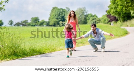 Mom, dad and daughter having walk on path in summer - stock photo