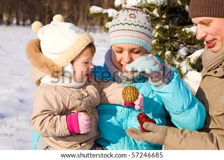 Mom, dad and daughter playing with Christmas decoration - stock photo