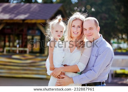 Mom, dad and daughter smiling in the summer on the background of wooden houses - stock photo