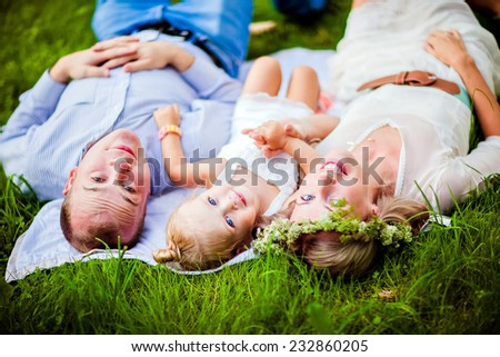Mom, dad and little daughter blonde lying together on the grass - stock photo