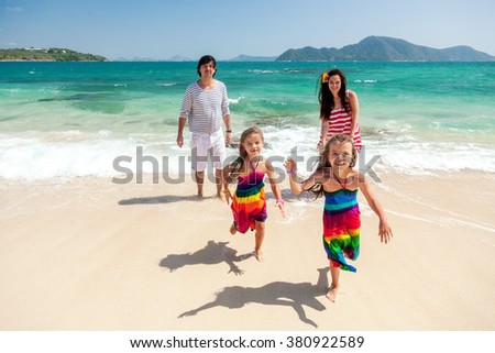 Mom, dad and two their children walking at the tropical beach, kids running - stock photo