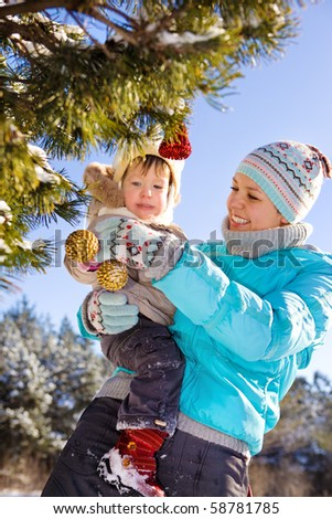 Mom decorating Christmas tree with her daughter - stock photo