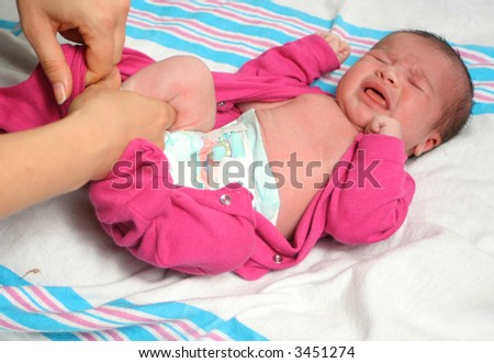 mom dresses up a newborn baby girl in a sleeper after a diaper change - stock photo