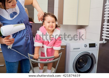 Mom dries the hair of his daughter a hairdryer in the bathroom. The concept of care, hygiene, education. - stock photo