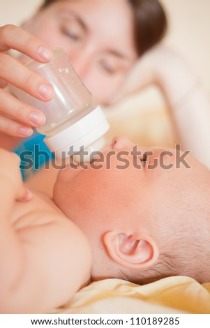 Mom feed baby with bottle in bed - stock photo