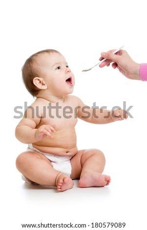 mom feeding baby  with a spoon - stock photo