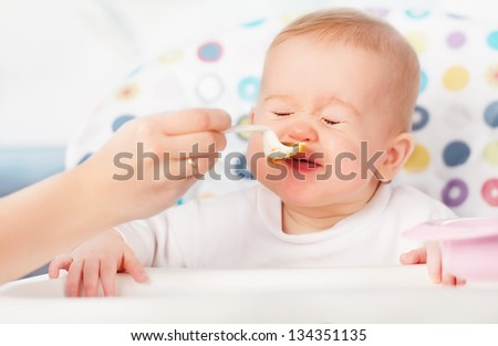 Mom feeds funny baby from a spoon - stock photo