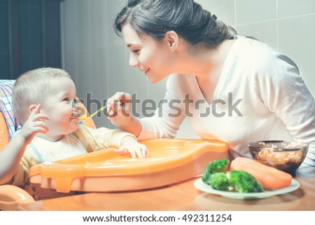 Mom feeds the baby soup. Healthy and natural baby food. Vegetables, carrots, cabbage, broccoli. Child sitting on the highchair at the table