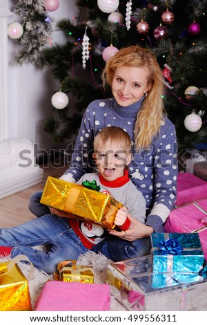 Mom gives a small child a Christmas gift on the Christmas tree background. Christmas presents
