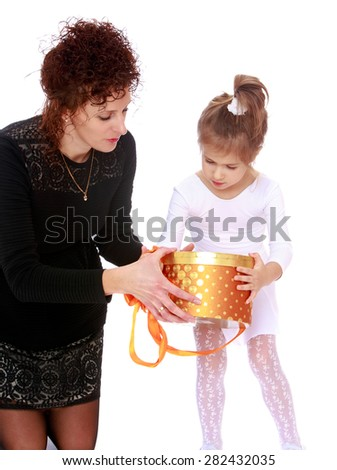 Mom gives daughter a present that is in a round box- isolated on white background - stock photo