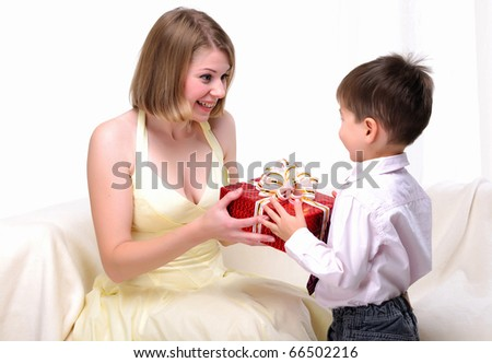 Mom giving a gift to his son sitting on a white sofa.