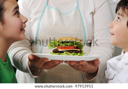 Mom giving snack to children - stock photo